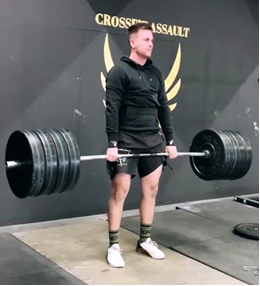 Athlete holding barbell with weights during Crossfit
