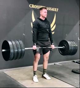 Sportler hält Langhantel mit Gewichten beim Crossfit
