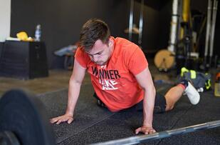 Athlete doing a pushup in an orange shirt